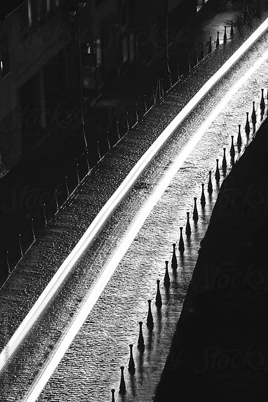 Car light trails on cobblestone street by Pixel Stories for Stocksy United
