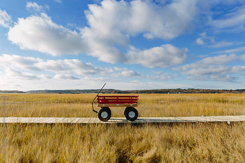 Red Wagon on Boardwalk in Autumn by Raymond Forbes LLC for Stocksy United