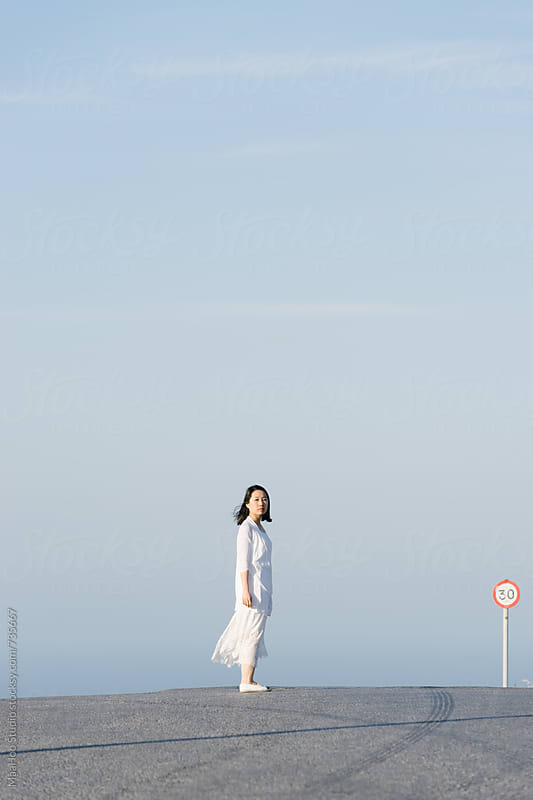 Chinese young girl walking on Santorini road by MaaHoo Studio for Stocksy United