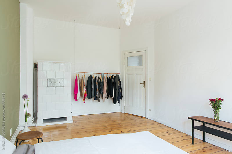 White Minimalist Bedroom With Female Clothes on Clothing Rail by Julien L. Balmer for Stocksy United