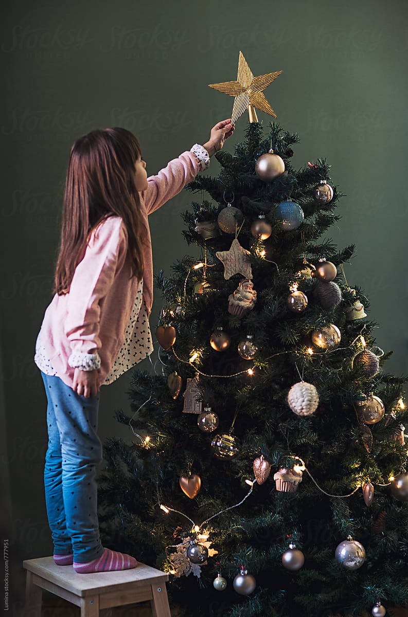 A Star For Christmas.Girl Puts A Star On Top Of The Christmas Tree By Lumina
