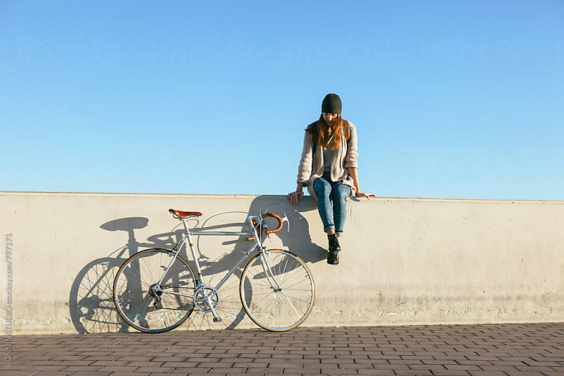 Woman sitting beside her vintage bicycle on a sunny winter day. by BONNINSTUDIO for Stocksy United