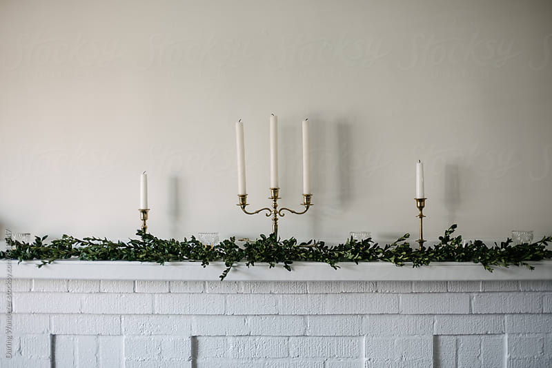 Green garland on white brick fireplace mantle with candle sticks for the holidays by Daring Wanderer for Stocksy United