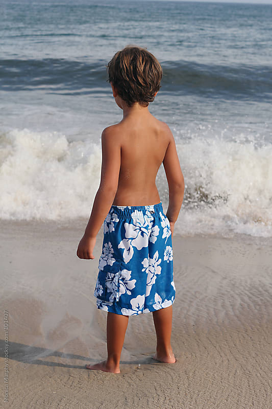 Young boy looking out at ocean by Monica Murphy for Stocksy United