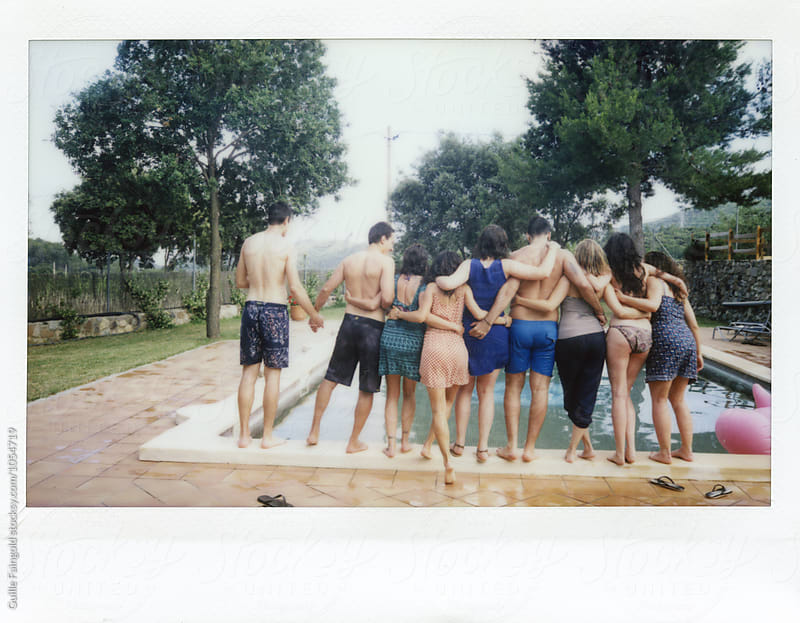 Back view of friends hugging while standing on pool's border by Guille Faingold for Stocksy United
