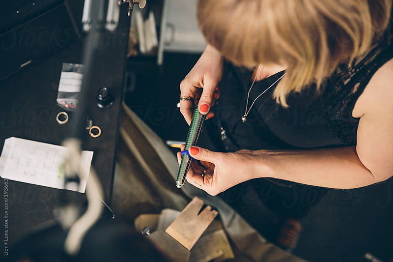 Closeup of a jewelry designer measuring a ring in her workshop by Lior + Lone for Stocksy United