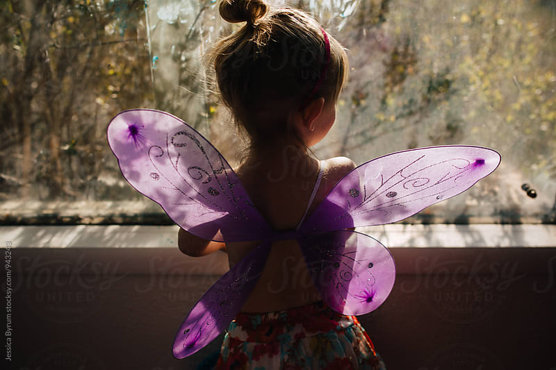 Little girl with butterfly wings in window by Jessica Byrum for Stocksy United