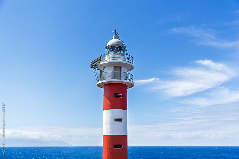 Red and white lighthouse with ocean background by ACALU Studio for Stocksy United