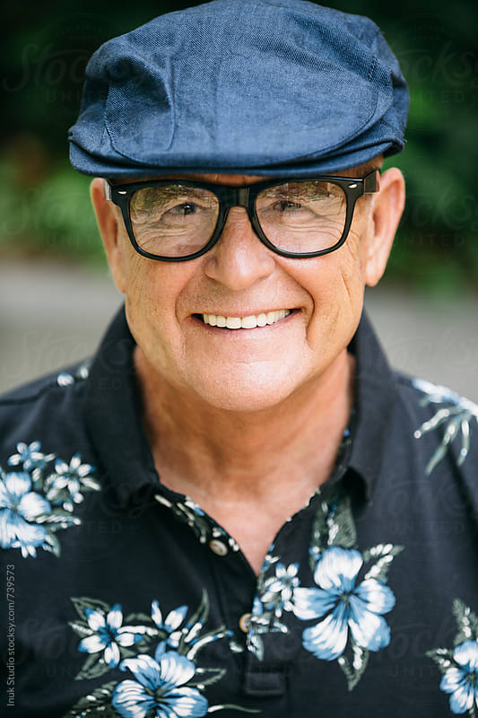Stylish senior man portrait smiling with a beret and glasses  by Inuk Studio for Stocksy United
