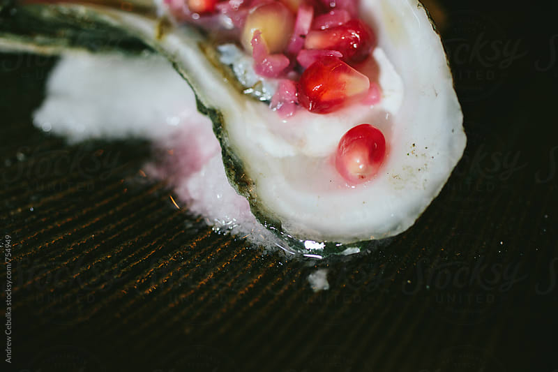 Oyster with pomegranate by Andrew Cebulka for Stocksy United