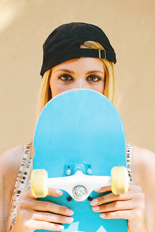 Young blonde girl with cap covering her face with skateboard. by BONNINSTUDIO for Stocksy United