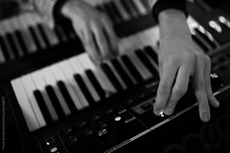 Two hands playing on two keyboards by Freek Zonderland for Stocksy United