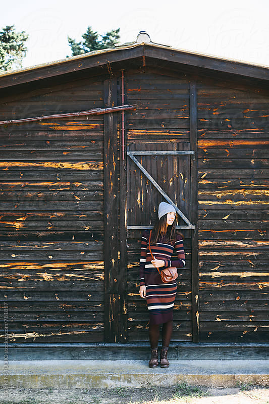 Hipster woman standing in front of a wooden cabin in the mountain. by BONNINSTUDIO for Stocksy United