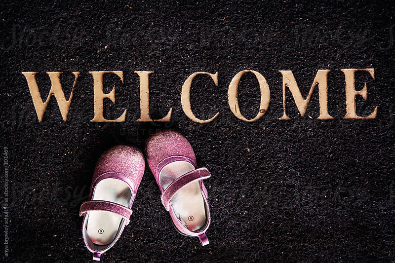 Pink toddler shoes on a welcome mat by anya brewley schultheiss for Stocksy United