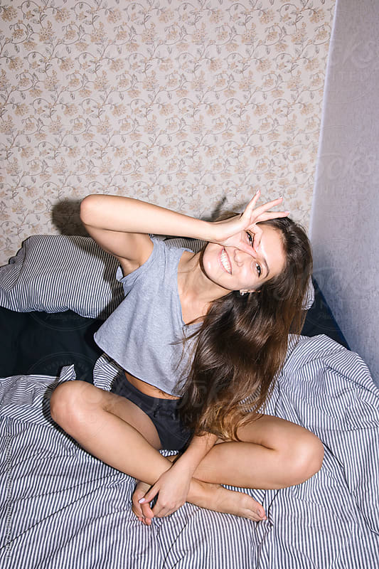 Young woman having fun while sitting on bed. by T-REX & Flower for Stocksy United