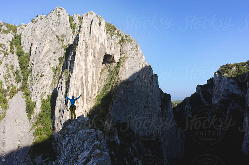 Happy strong woman standing on top of a rocky ridge by RG&B Images for Stocksy United