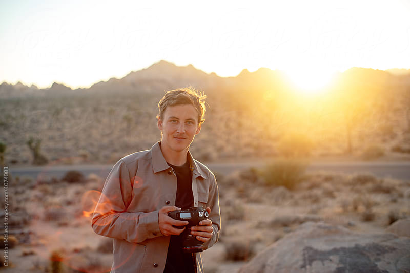 Guy in the desert at first light. by Christian McLeod Photography for Stocksy United