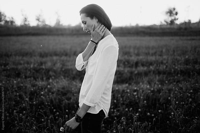 Young pensive girl  walking in the field by Evgenij Yulkin for Stocksy United