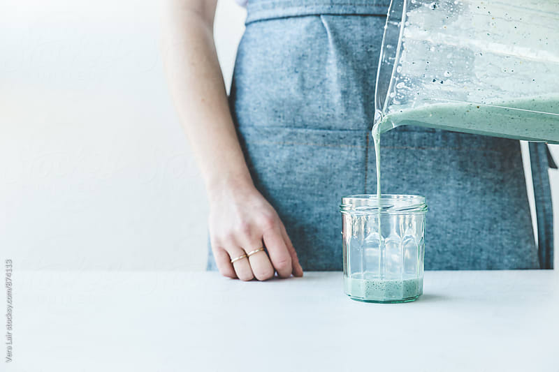 Woman's hand serving a seaweed smoothie by Vera Lair for Stocksy United