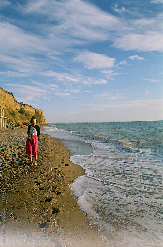 A film portrait of young woman dressing bright clothes in the seashore by Anna Malgina for Stocksy United