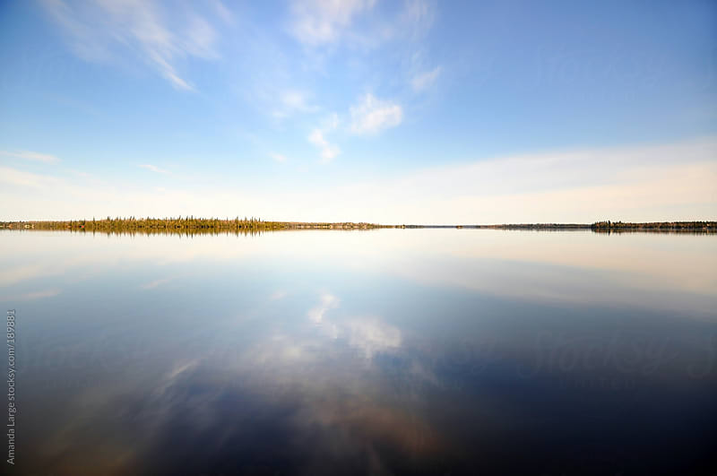 Sunny sky reflected in a still lake in Northern Ontario. by Amanda Large for Stocksy United