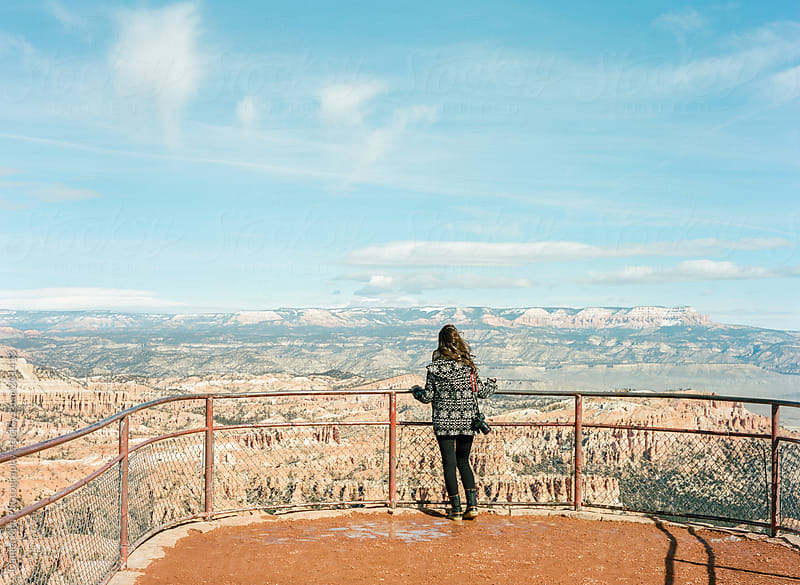 young woman overlooking snow capped canyon by Daniel Kim Photography for Stocksy United