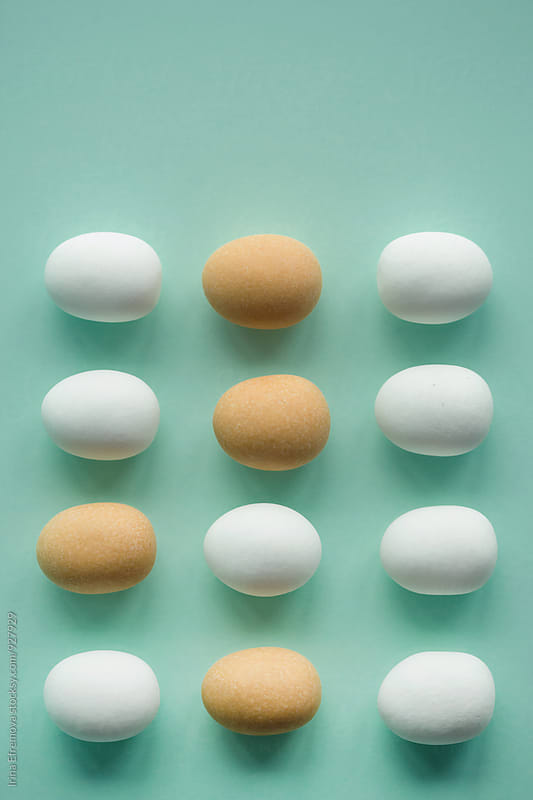 White and brown  egg shaped candies on the light turquoise background by Irina Efremova for Stocksy United