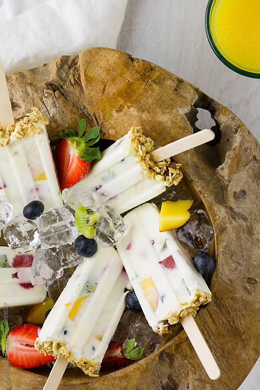 Bowl of yogurt and fruit ice lollies in ice and fruit by Kirsty Begg for Stocksy United