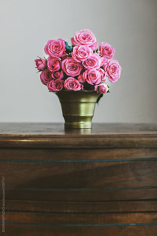 Bouquet of a pink roses in a vintage gold vase on a wood table.  by BONNINSTUDIO for Stocksy United