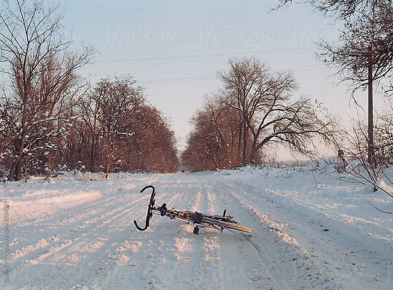 Bicycle lying on the snowy road by Sasha Evory for Stocksy United