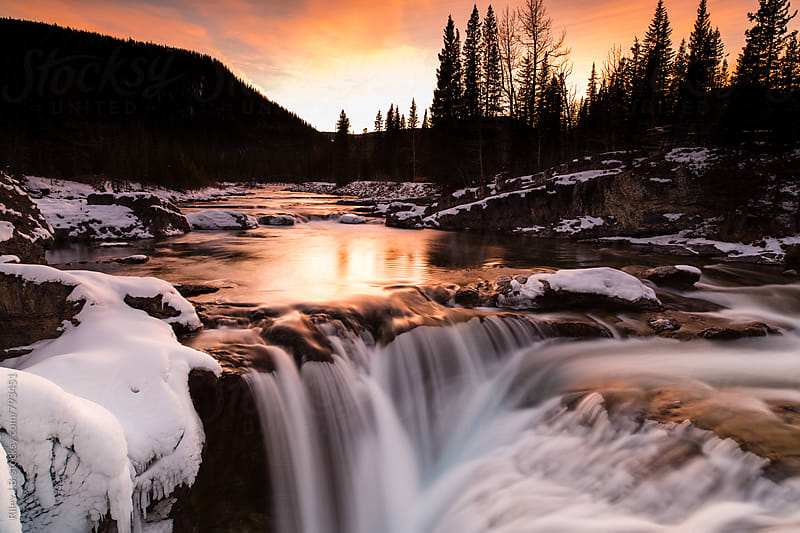 A long exposure of a creek flowing into a waterfall at sunset. by Riley J.B. for Stocksy United