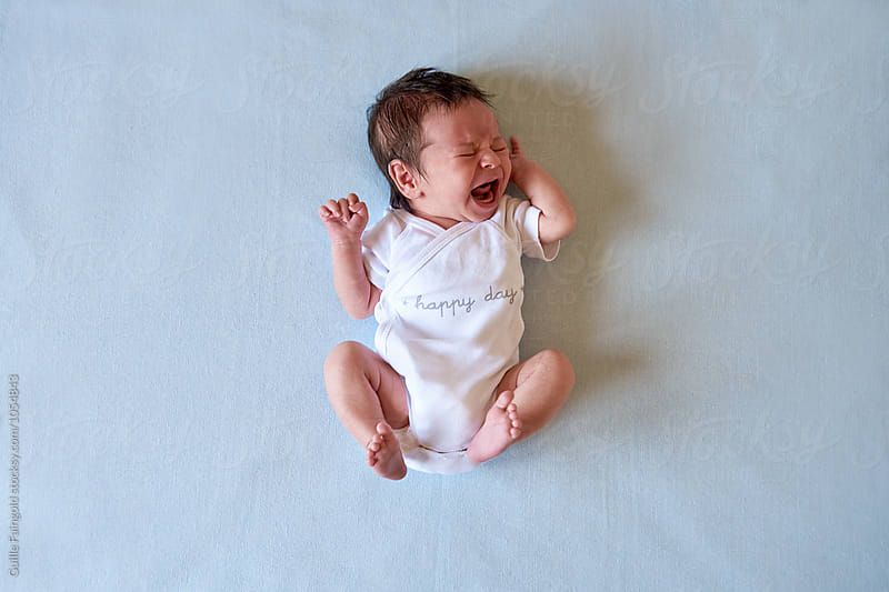 Crying baby on white sheets by Guille Faingold for Stocksy United