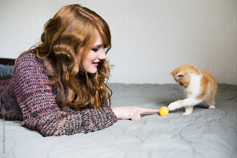 Beautiful young woman is playing with her kitten by Jovana Rikalo for Stocksy United