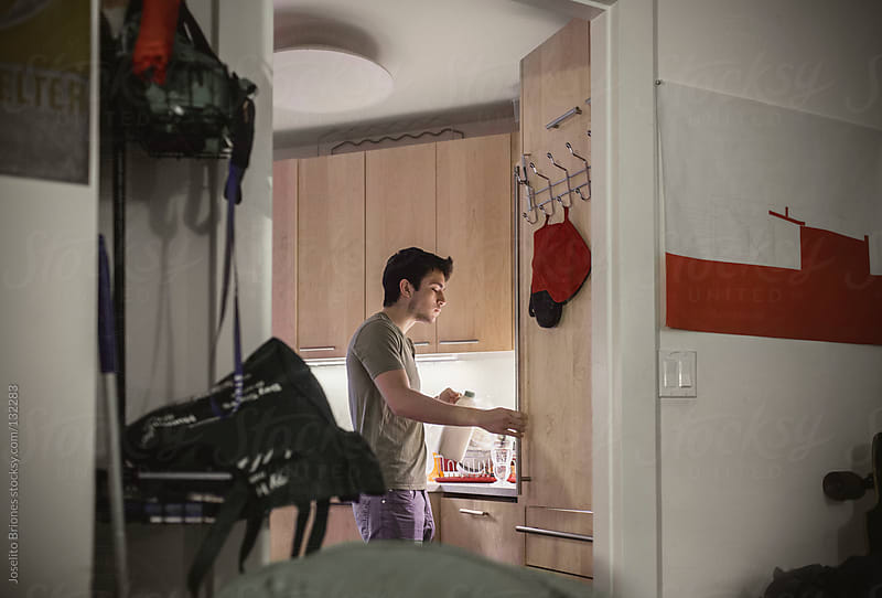 Mexican-American Male University Student Makes Breakfast in New York Apartment Kitchen by Joselito Briones for Stocksy United