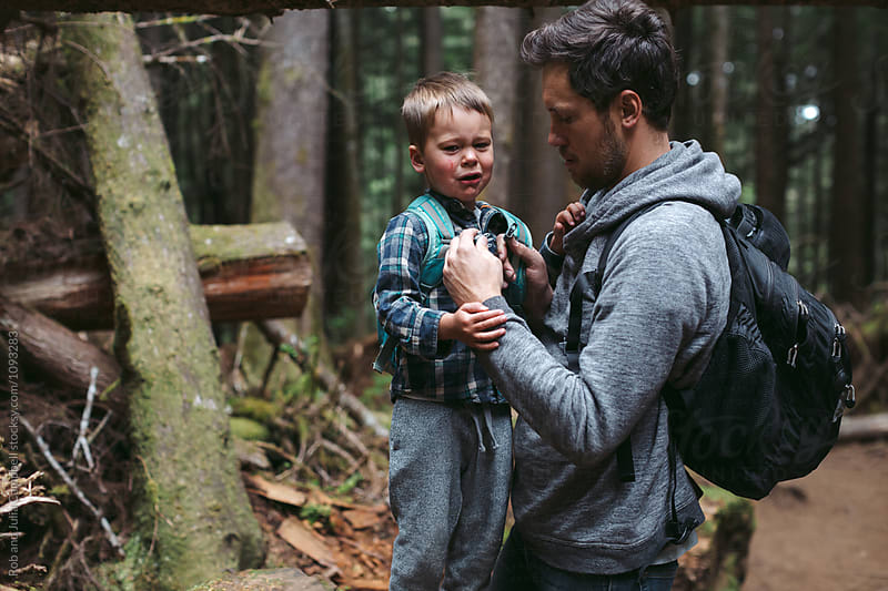 Young caucasian dad spending time with kids outdoors by Rob and Julia Campbell for Stocksy United