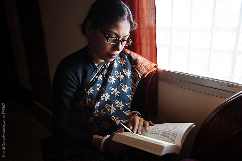 Young woman reading a book by the window by Saptak Ganguly for Stocksy United