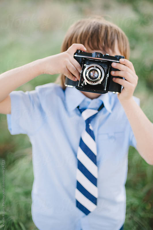 Young stylish boy playing with an old camera by Kristin Rogers Photography for Stocksy United