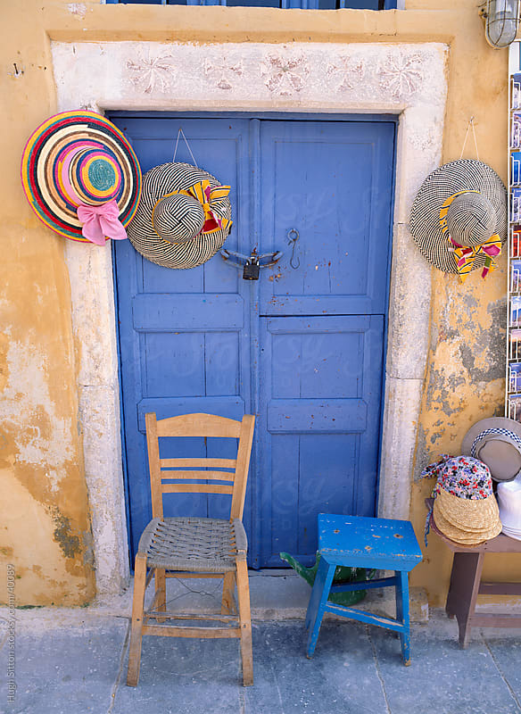 Hats hanging up for sale against blue door. Greece. by Hugh Sitton for Stocksy United