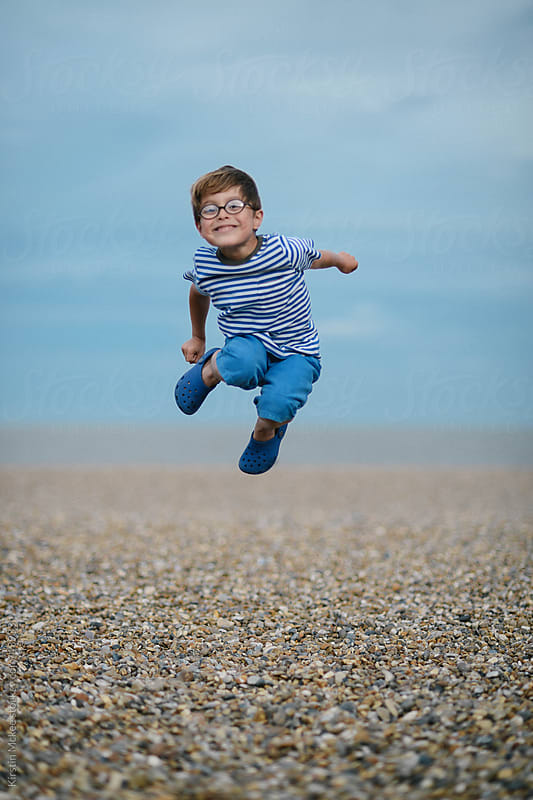 A caucasian boy jumps for joy on a stony beach by Kirstin Mckee for Stocksy United