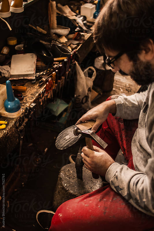 Shoemaker working in his workshop. by Audrey Shtecinjo for Stocksy United