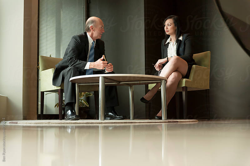 A male and female executive impromptu meeting by Ben Ryan for Stocksy United
