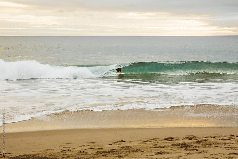 Surfer riding a wave and in the barrel by Curtis Kim for Stocksy United