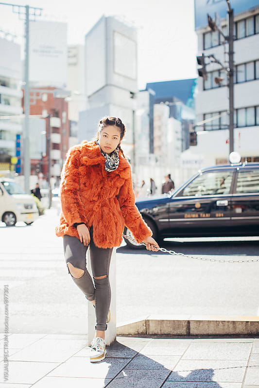 Outdoor Portrait of Young Pretty Asian Woman in Red Fur Coat Standing in Tokyo Street by VISUALSPECTRUM for Stocksy United
