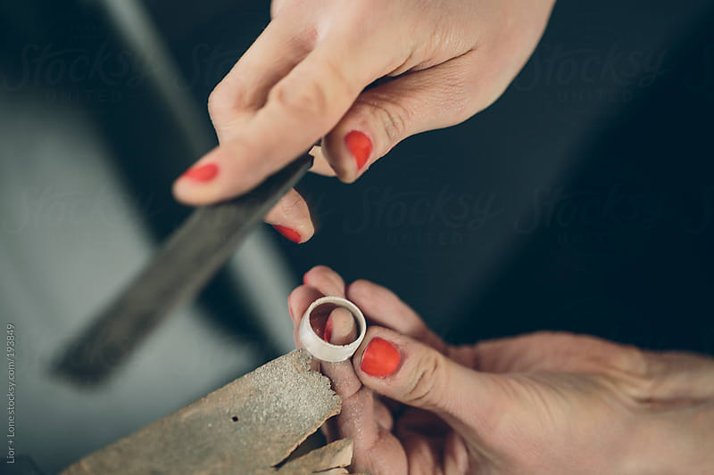 Closeup of a woman's hands polishing a silver ring by Lior + Lone for Stocksy United
