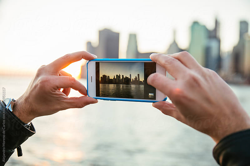 Hands taking photograph of New York in the morning by Alejandro Moreno de Carlos for Stocksy United