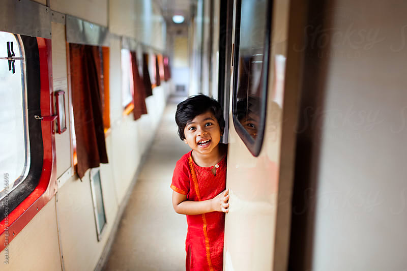 Little girl peeking from behind the door and smiling by Saptak Ganguly for Stocksy United