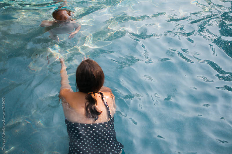 A child swimming to his mother by Chelsea Victoria for Stocksy United