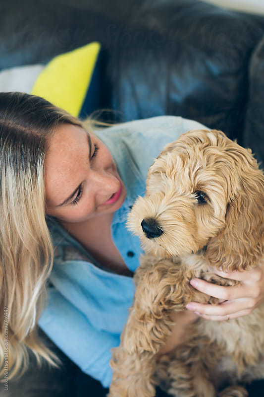 Young Woman Holding Pet Labradoodle Puppy by Luke Mattson for Stocksy United