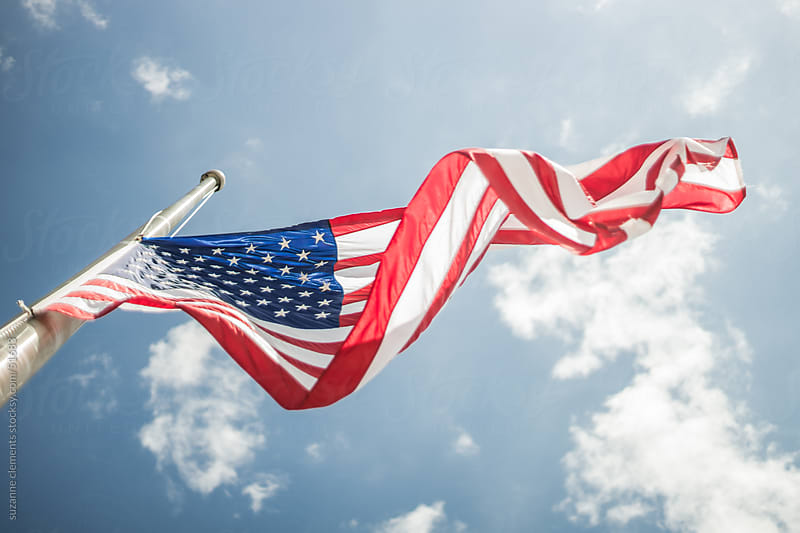 American Flag Against a Blue Sky by suzanne clements for Stocksy United