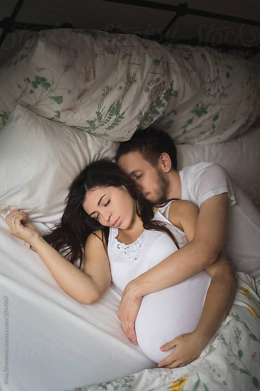 Expecting couple sleeping by Irina Efremova for Stocksy United